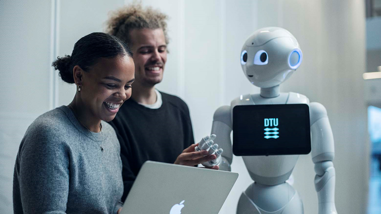 A female and a male student of Technical University of Denmark, talking to a 120-centimetre tall humanoid robot, which is to carry out teaching and research tasks.
